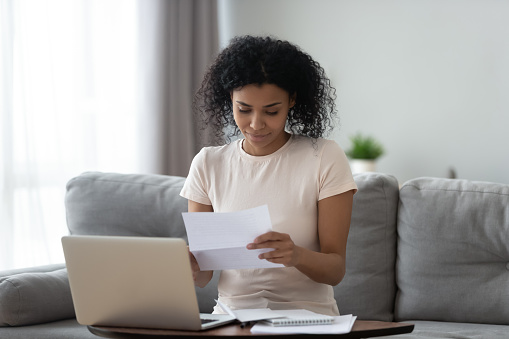 istock Smiling african girl student reading paper letter sit on sofa 1162624158