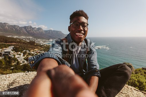 istock Smiling african guy on top of a mountain taking selfie 911812356
