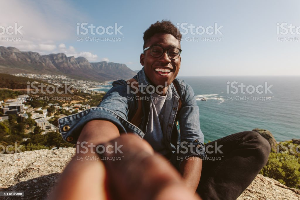 Smiling african guy on top of a mountain taking selfie stock photo