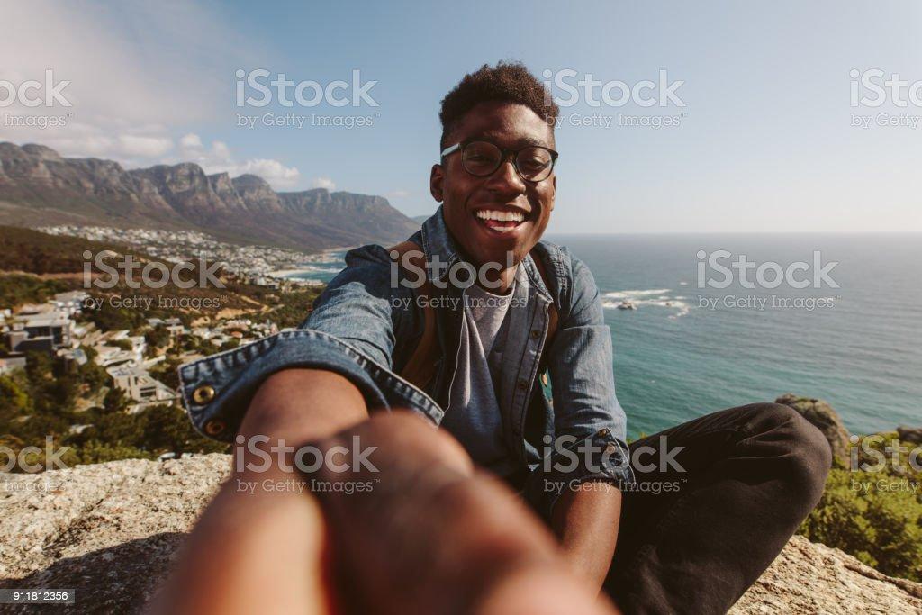 Chico africano sonriente encima de una montaña tomando selfie - foto de stock