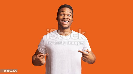 Clothes Template. Happy black man pointing at white t-shirt, mockup for logo or branding design
