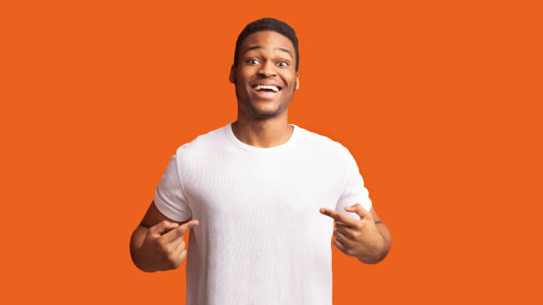 Smiling african guy pointing at his t-shirt Clothes Template. Happy black man pointing at white t-shirt, mockup for logo or branding design white t shirt stock pictures, royalty-free photos & images