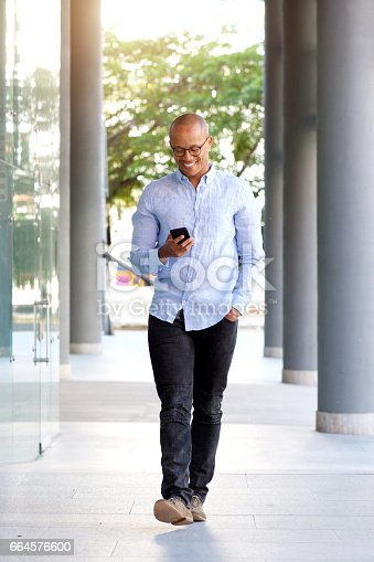 Full length portrait of smiling african guy walking with mobile phone