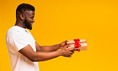 istock Smiling african guy with gift box over yellow studio background 1171063040