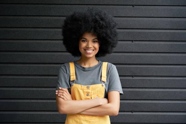 笑顔のアフリカのヒップスターの女性は、黒い壁に交差した腕を立っていました。 - gen z ストックフォトと画像