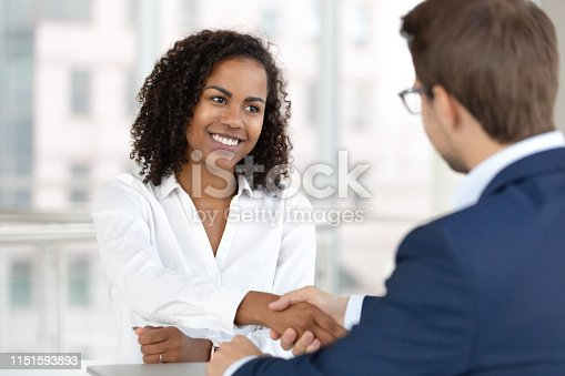 Smiling african female hr manager handshake hire male candidate at job interview make good first impression, happy mixed race client shake hand of bank broker, respect, business agreement concept