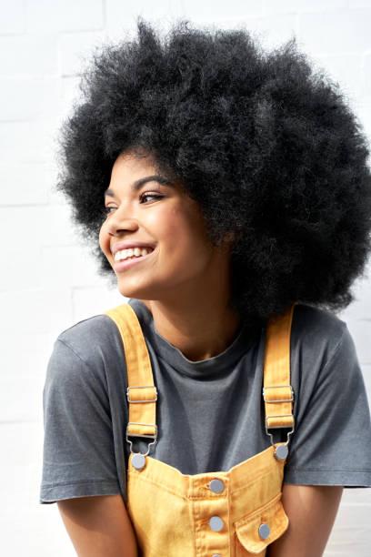 白い背景に立って笑うアフロの髪を持つ笑顔のアフリカの女性。 - gen z ストックフォトと画像