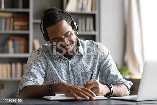 istock Smiling african male student professional wear headset elearning making notes 1203044159