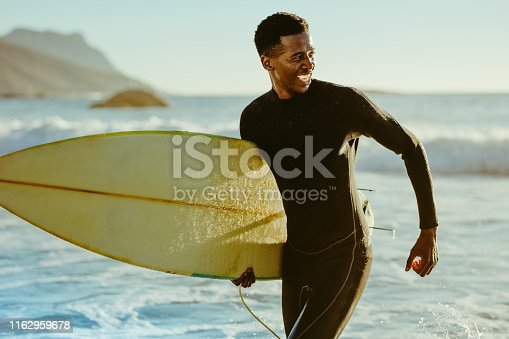 Smiling african male running out of the ocean after water surfing. Happy young man with surfboard on the beach enjoying holidays.