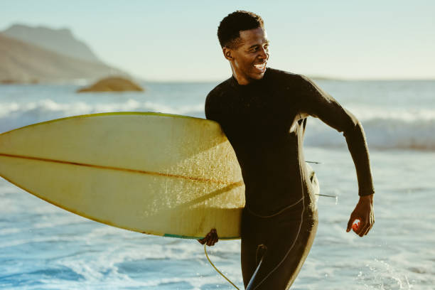 Smiling african male surfer Smiling african male running out of the ocean after water surfing. Happy young man with surfboard on the beach enjoying holidays. wetsuit stock pictures, royalty-free photos & images
