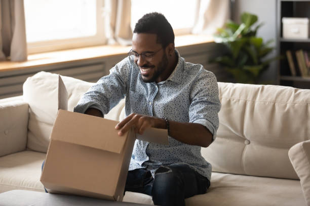 Smiling african man customer opening cardboard box parcel on sofa Smiling millennial african american man customer opening cardboard box sit on sofa at home, happy ethnic male consumer unpack parcel receive retail purchase fast postal shipping delivery concept package stock pictures, royalty-free photos & images