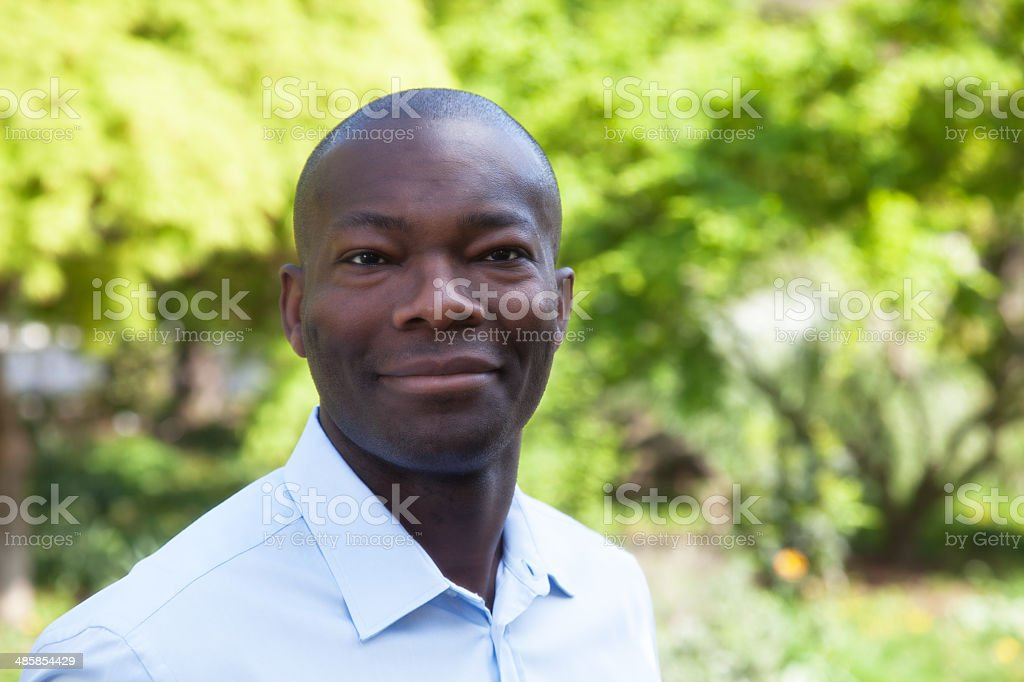 Smiling african man in a park stock photo