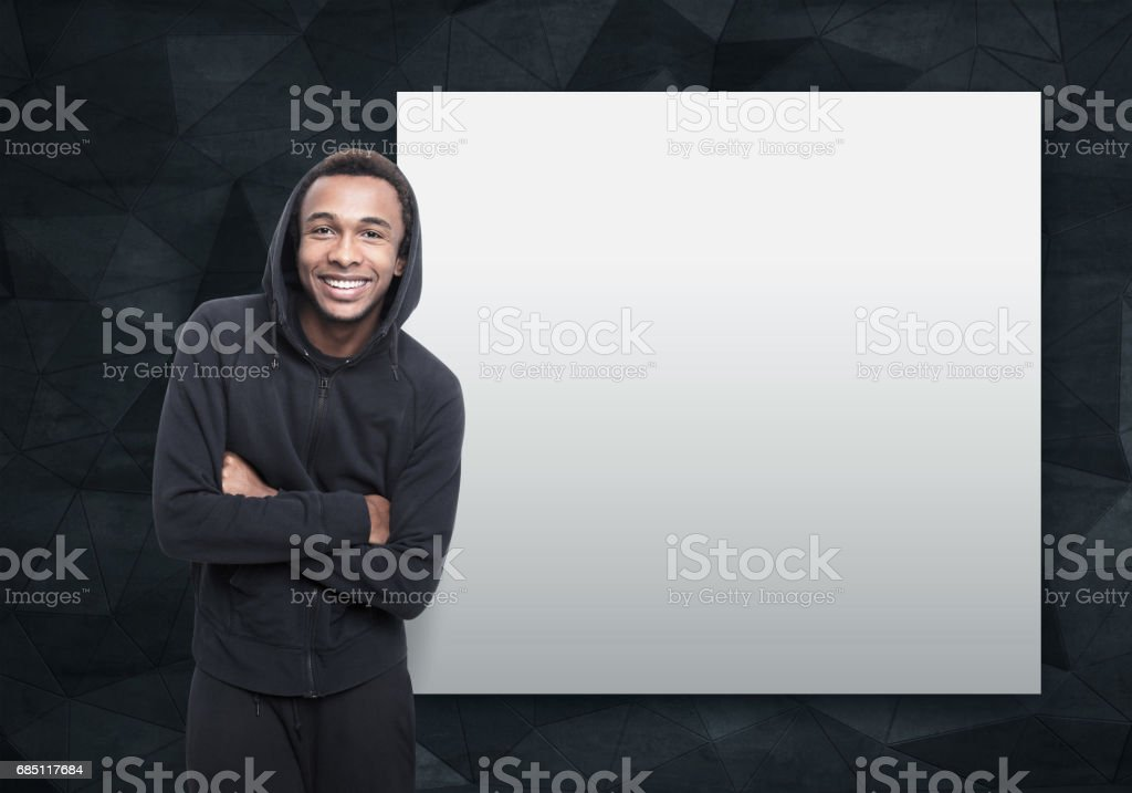 Smiling African man near a blank poster stock photo