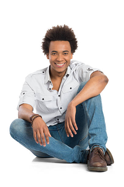Smiling African Man Sitting Portrait Of Happy Young African Man Sitting Isolated On White Background cross legged stock pictures, royalty-free photos & images