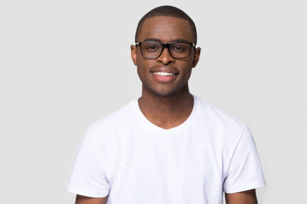 smiling african millennial man looking at camera isolated on background - ritratto uomo foto e immagini stock