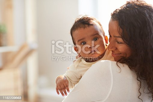 Smiling loving young African mom with curly hair standing in room and holding adorable baby boy with chubby cheeks