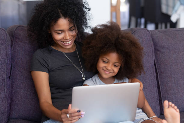 Smiling african mother and kid daughter having fun with computer stock photo