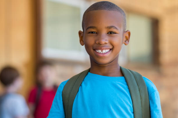 Smiling african school boy Smiling african american school boy with backpack looking at camera. Cheerful black kid wearing green backpack with a big smile. Elementary and primary school education. 8 9 years stock pictures, royalty-free photos & images