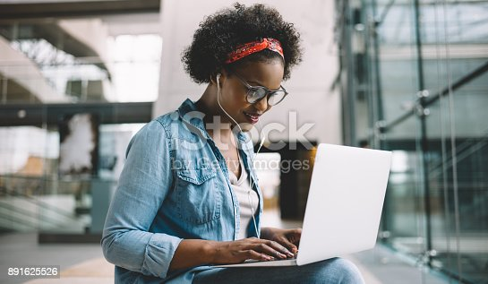 istock Smiling African student studying for an exam on campus 891625526