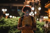 Young African student is texting message on smart phone outdoors at night.