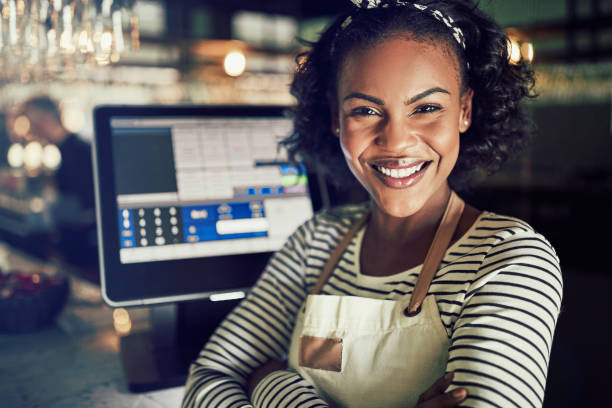 Smiling African waitress standing by a point of sale terminal Smiling young African waitress wearing an apron standing by a point of sale terminal while working in a trendy restaurant sales clerk stock pictures, royalty-free photos & images