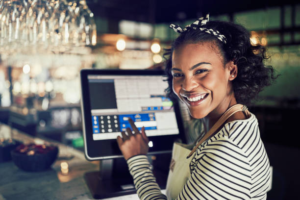Smiling African waitress using a restaurant point of sale terminal Smiling young African waitress wearing an apron using a touchscreen point of sale terminal while working in a trendy restaurant cash register stock pictures, royalty-free photos & images
