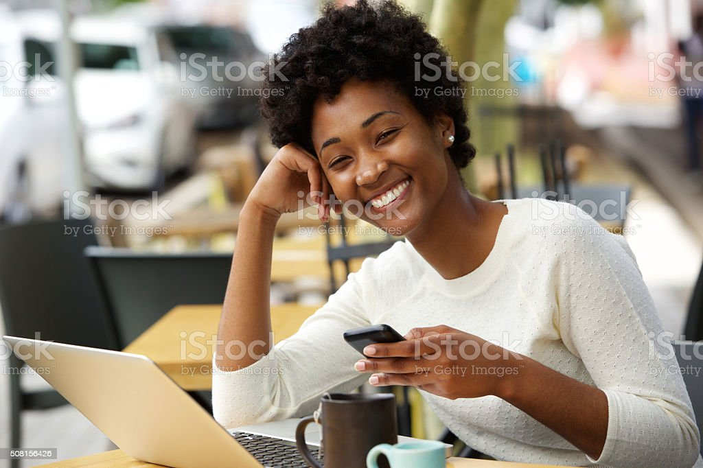 Smiling african woman at cafe with a mobile phone stock photo