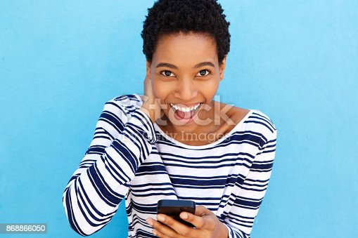 istock smiling african woman holding smart phone 868866050