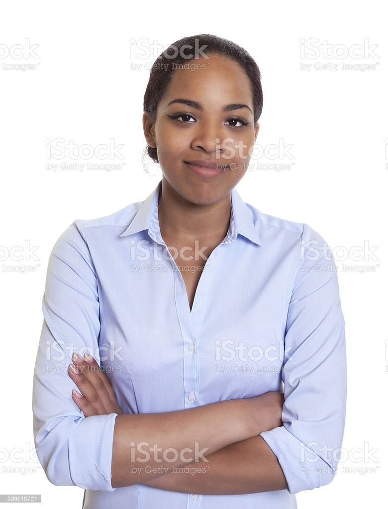 Smiling african woman in a blue shirt with crossed arms stock photo