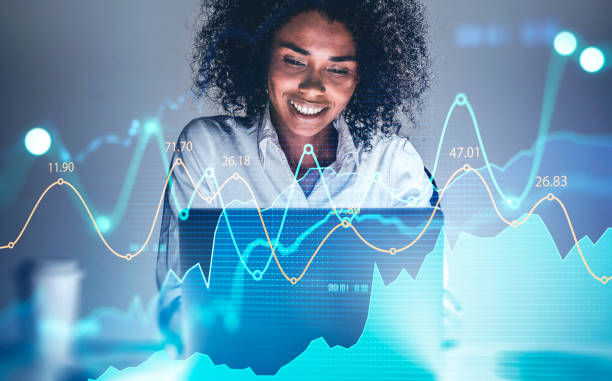 Smiling African woman in office, financial chart stock photo