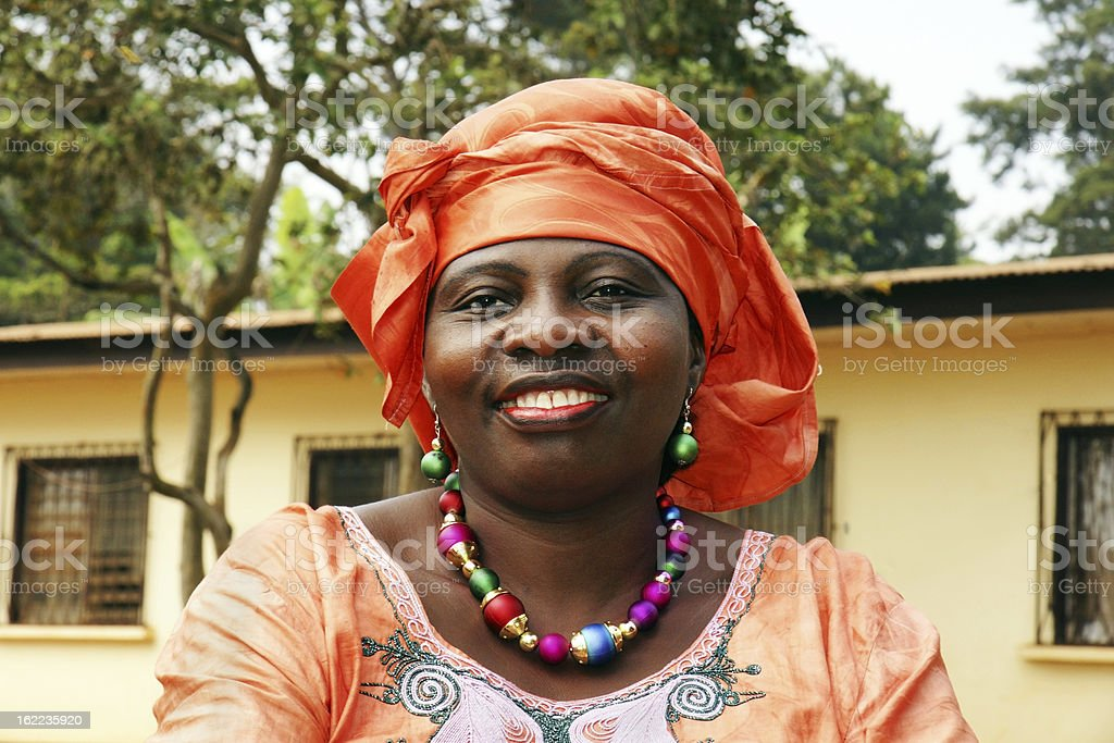Smiling African woman in orange scarf stock photo