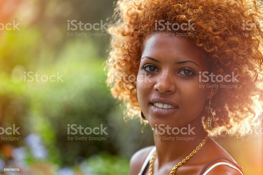 Smiling African woman in sunshine Outdoors profile portrait stock photo