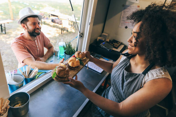 Lächelnde afrikanische Frau verkauft Burger in Food-Truck – Foto