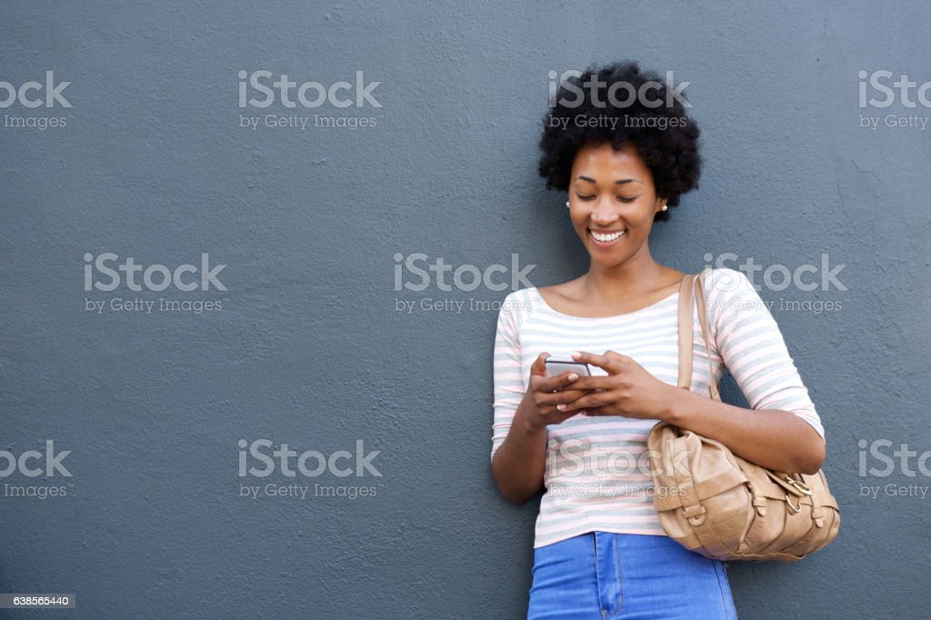 Smiling african woman with bag looking at mobile phone stock photo