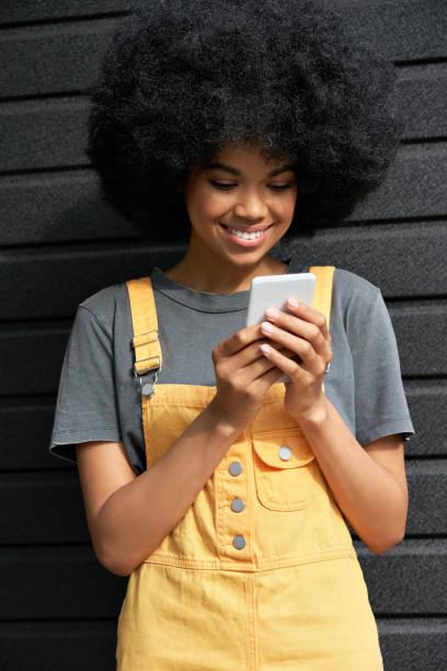 スマートフォンを使用してアフロの髪を持つ笑顔アフリカの若いヒップスターの女性。 - gen z ストックフォトと画像