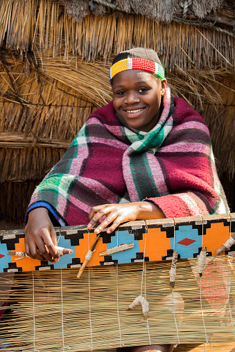 istock Smiling African Zulu woman in ethnic clothes weaves straw carpet. 519338666