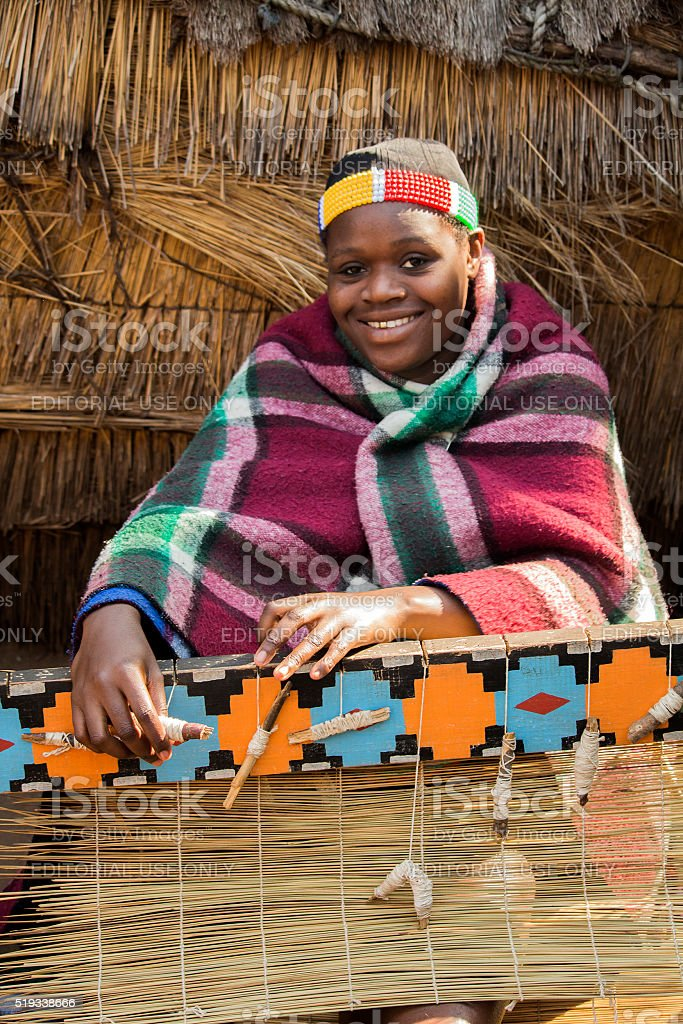 Smiling African Zulu woman in ethnic clothes weaves straw carpet. stock photo