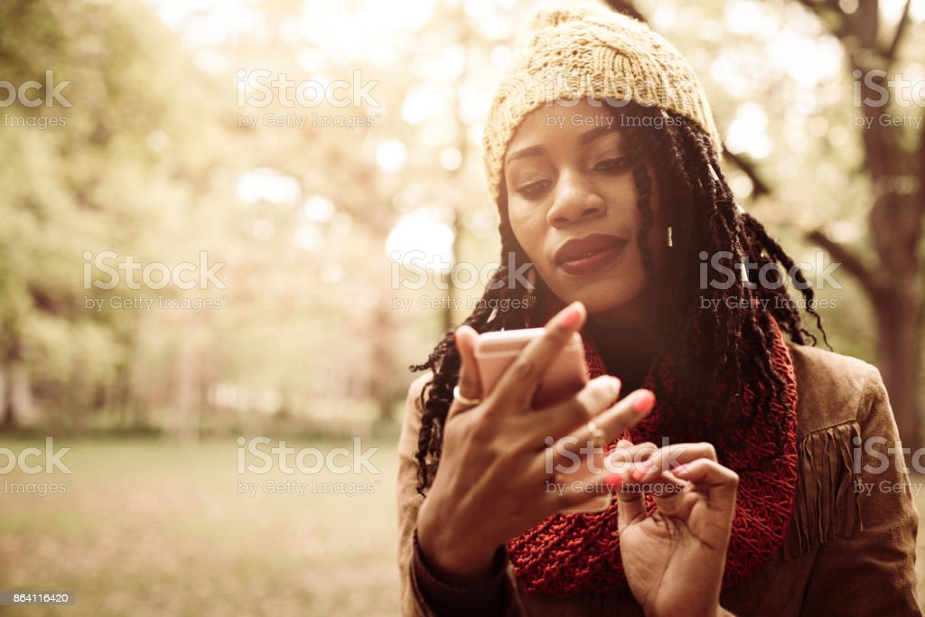Smiling Africana American girl standing in park and typing on mobile phone. royalty-free stock photo