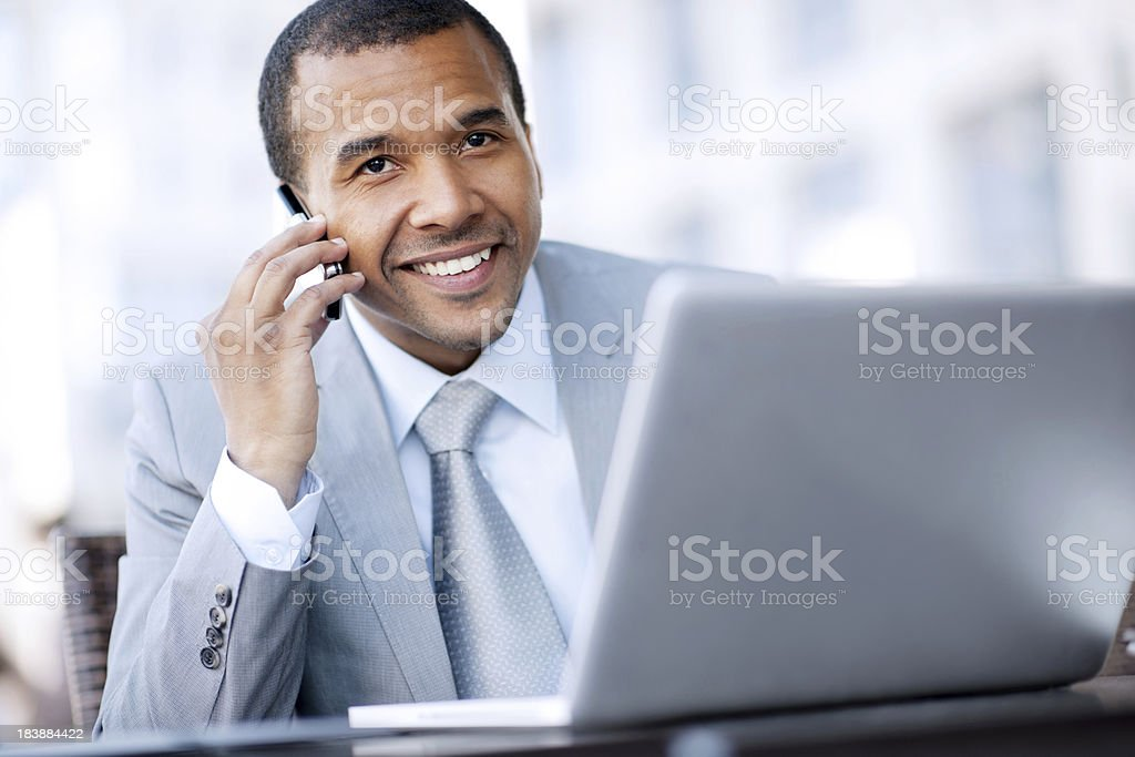 Smiling African-American businessman talking on a mobile phone. royalty-free stock photo