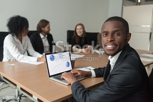 istock Smiling african-american businessman using laptop looking at camera at meeting 923040174