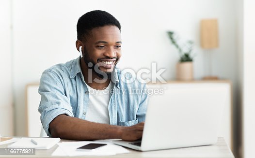 istock Smiling african-american guy in earphones studying foreign language online 1166775921