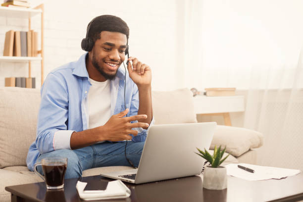 Smiling african-american guy in headphones looking at laptop Smiling african-american guy in headphones studying foreign language online through video conference application, copy space male likeness stock pictures, royalty-free photos & images