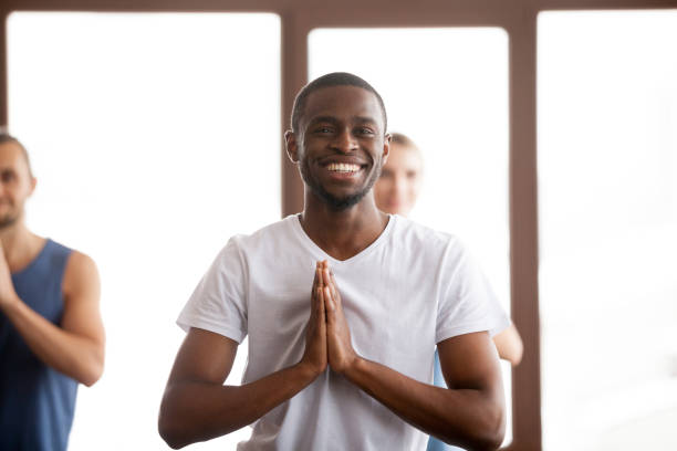 Smiling african-american man holding hands in namaste at group training Smiling african-american man holding hands in namaste gesture, happy black positive guy ready to start practicing yoga meditation exercises at group training class together with multiracial people prayer pose yoga stock pictures, royalty-free photos & images