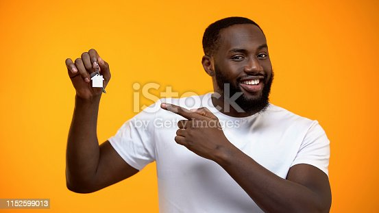 istock Smiling African-American man pointing finger into house keys, real estate 1152599013