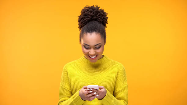 smiling african-american woman chatting on smartphone, modern technology, app - messaggistica online foto e immagini stock