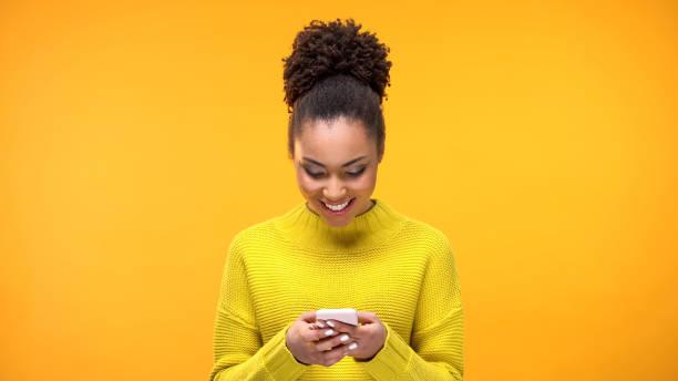 lächelnde afroamerikanerin im chat auf dem smartphone, moderne technik, app - instant messaging stock-fotos und bilder