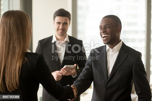 istock Smiling afro american businessman and caucasian businesswoman handshaking, first impression 695760088