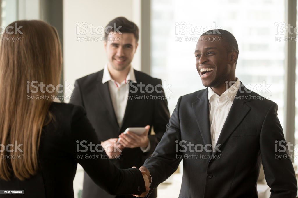 Smiling afro american businessman and caucasian businesswoman handshaking, first impression stock photo