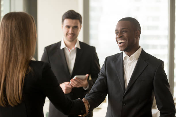 smiling afro american businessman and caucasian businesswoman handshaking, first impression - new stock photos and pictures