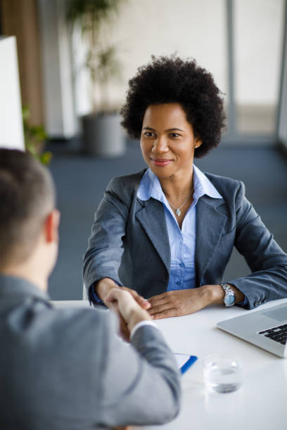 Smiling Afro American businesswoman and Caucasian businessman handshaking stock photo